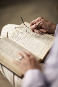 Senior woman reading Bible, holding spectacles, close-up of hands