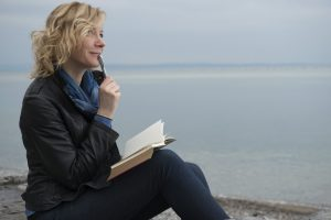 Poet by the sea with a journal