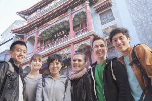 Group of young people with Chinese architecture in background, portrait.
