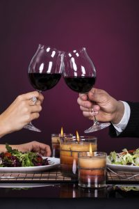 Couple Tossing Wine Glass at a Restaurant